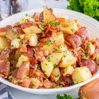 Square image of German potato salad in white bowl topped with parsley