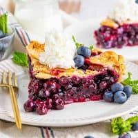 Square image of slice of Homemade Blueberry Pie on white plate topped with whipped cream