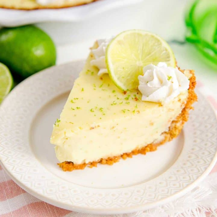 Square image of a slice of Key Lime Pie on white plate close up with whipped cream and lime