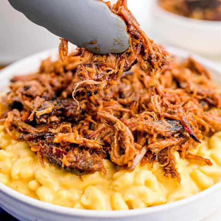 Square image of pulled pork being added to macaroni and cheese