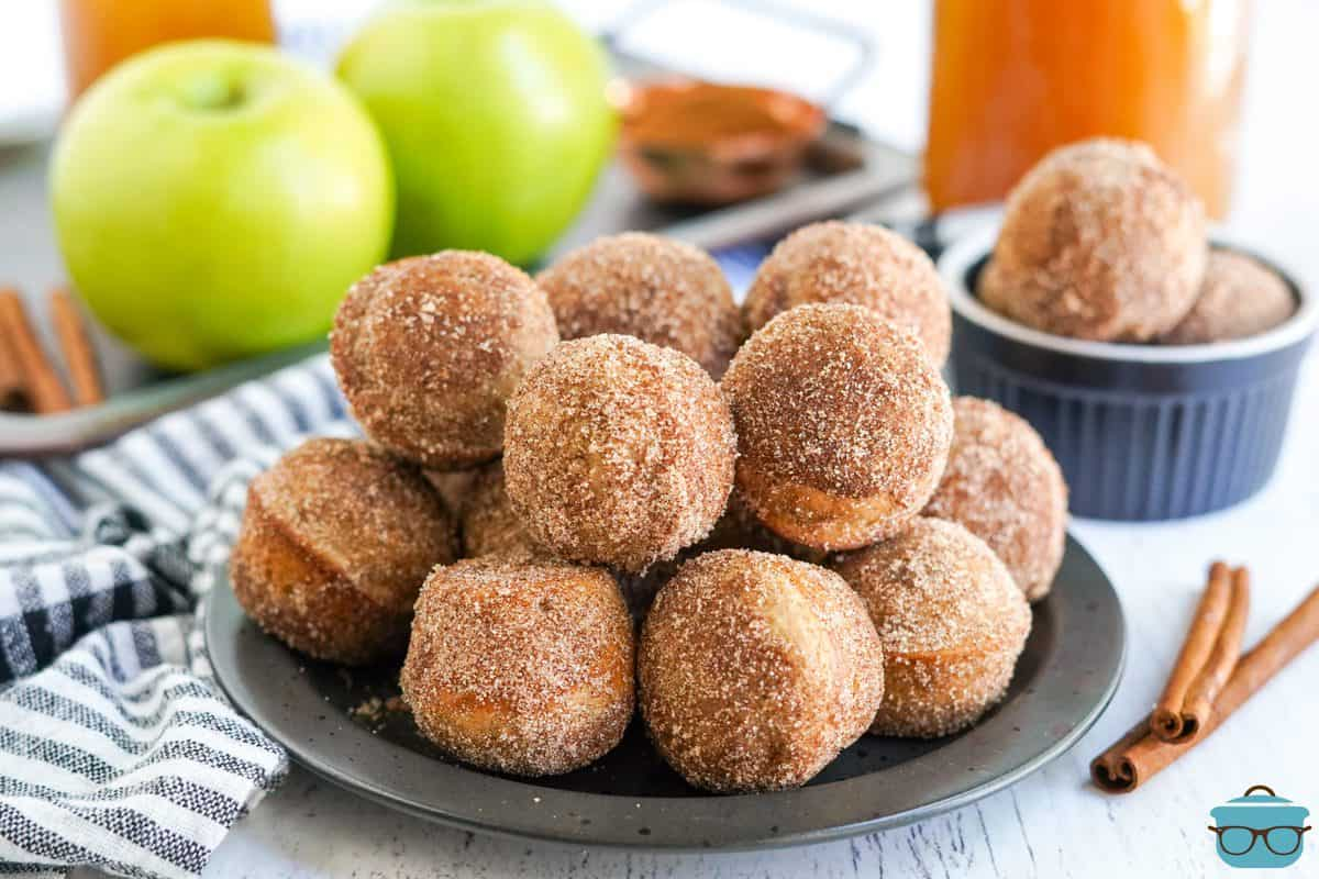 Apple Cider Donut Holes stacked on black plate with apples behind plate.