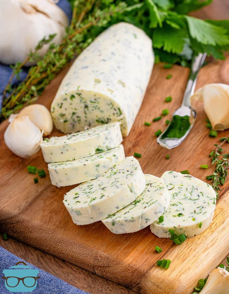 Garlic herb butter sliced in rounds on wooden board with herbs as garnish.