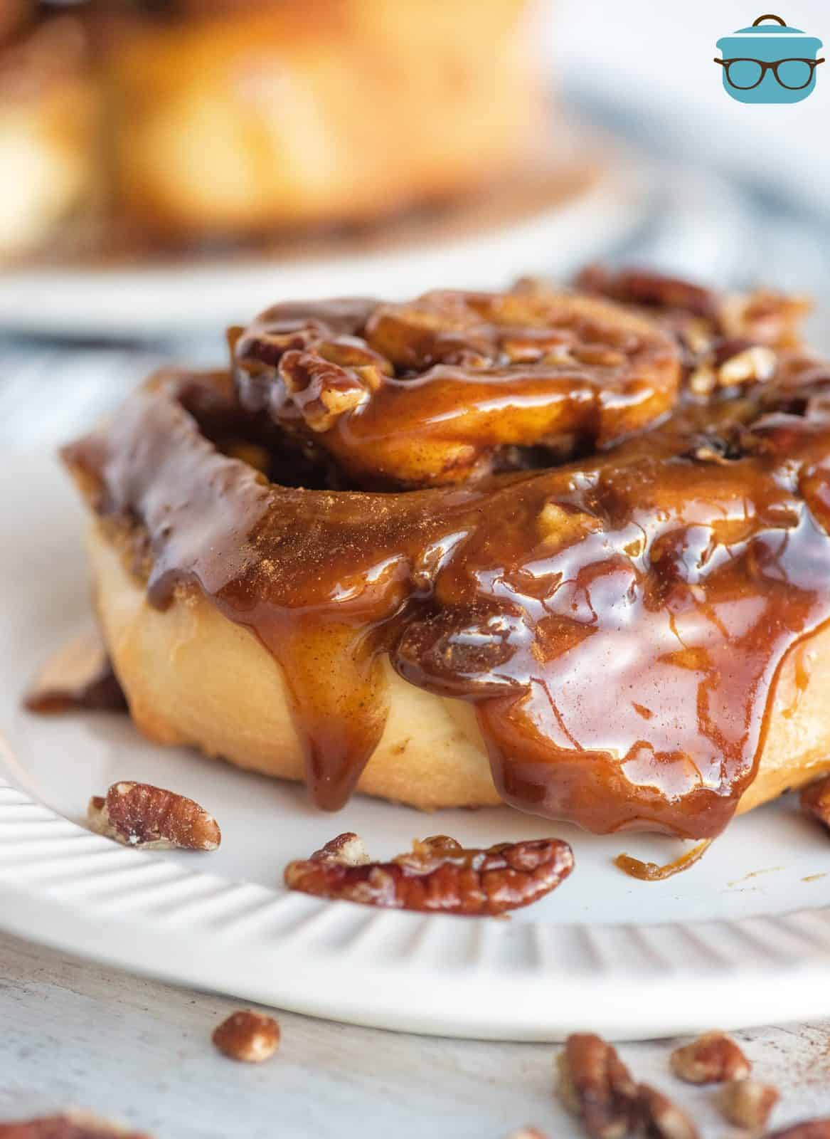 Homemade Sticky Bun with dripping sauce on white plate.