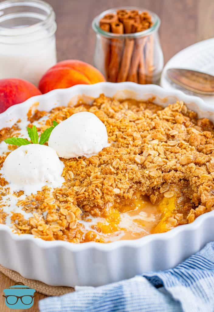 Fresh Easy Peach Crisp in baking dish with some of the crisp removed.
