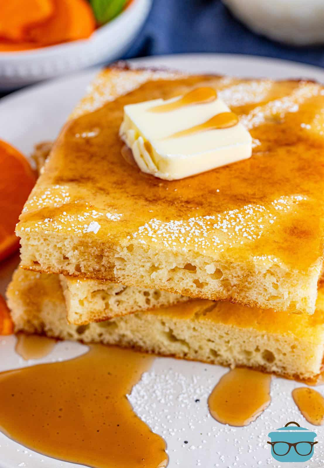 Three stacked slices of Sheet Pan Pancakes with butter and syrup.