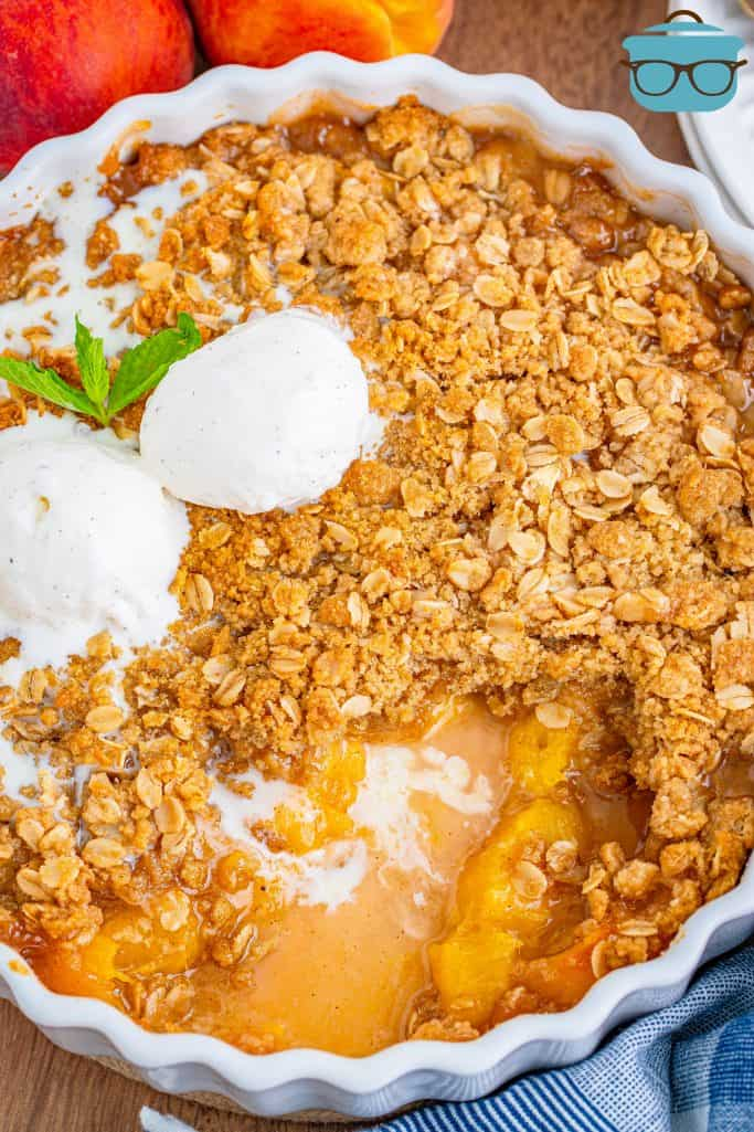 Overhead of Peach Crisp in baking dish with ice cream on top with some crisp removed.