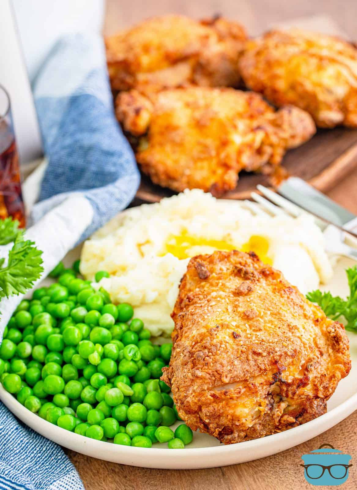 On piece of Air Fried Chicken on plate with peas and potatoes.