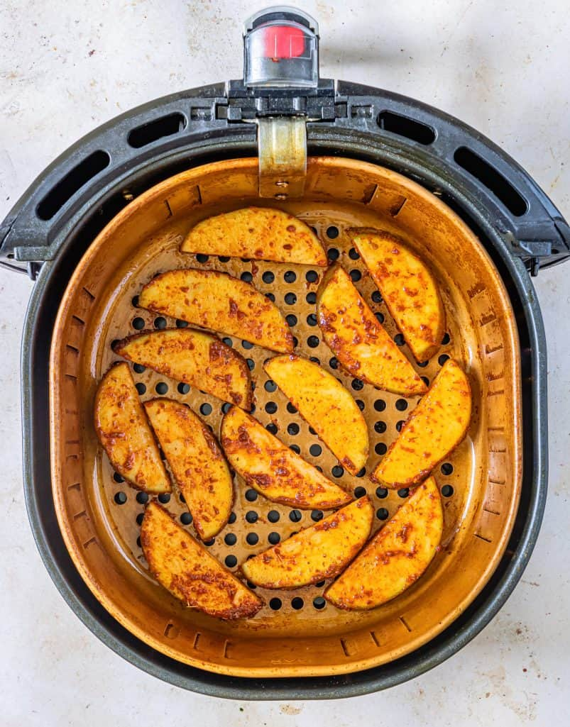 Coated potato wedges in air fryer basket.