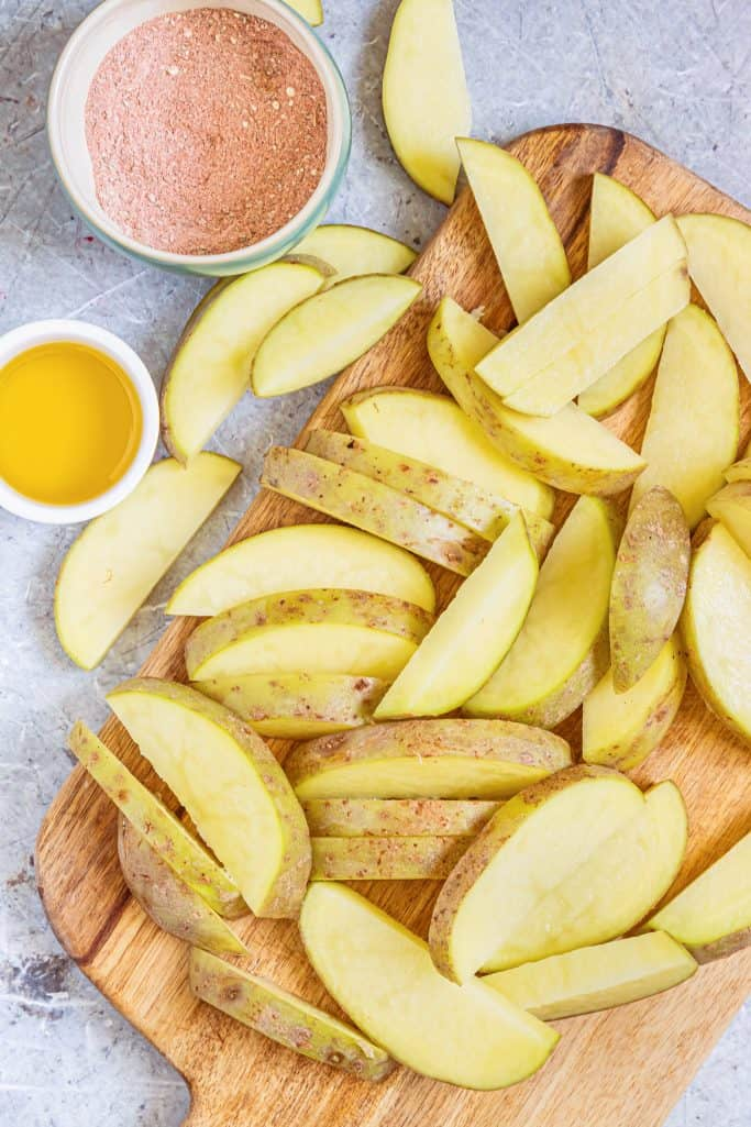 Cut up potatoes into wedges.