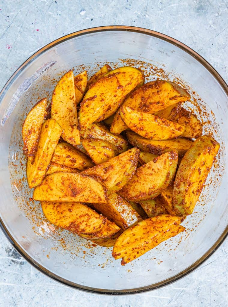 Potato wedges coated in herbs and spices.