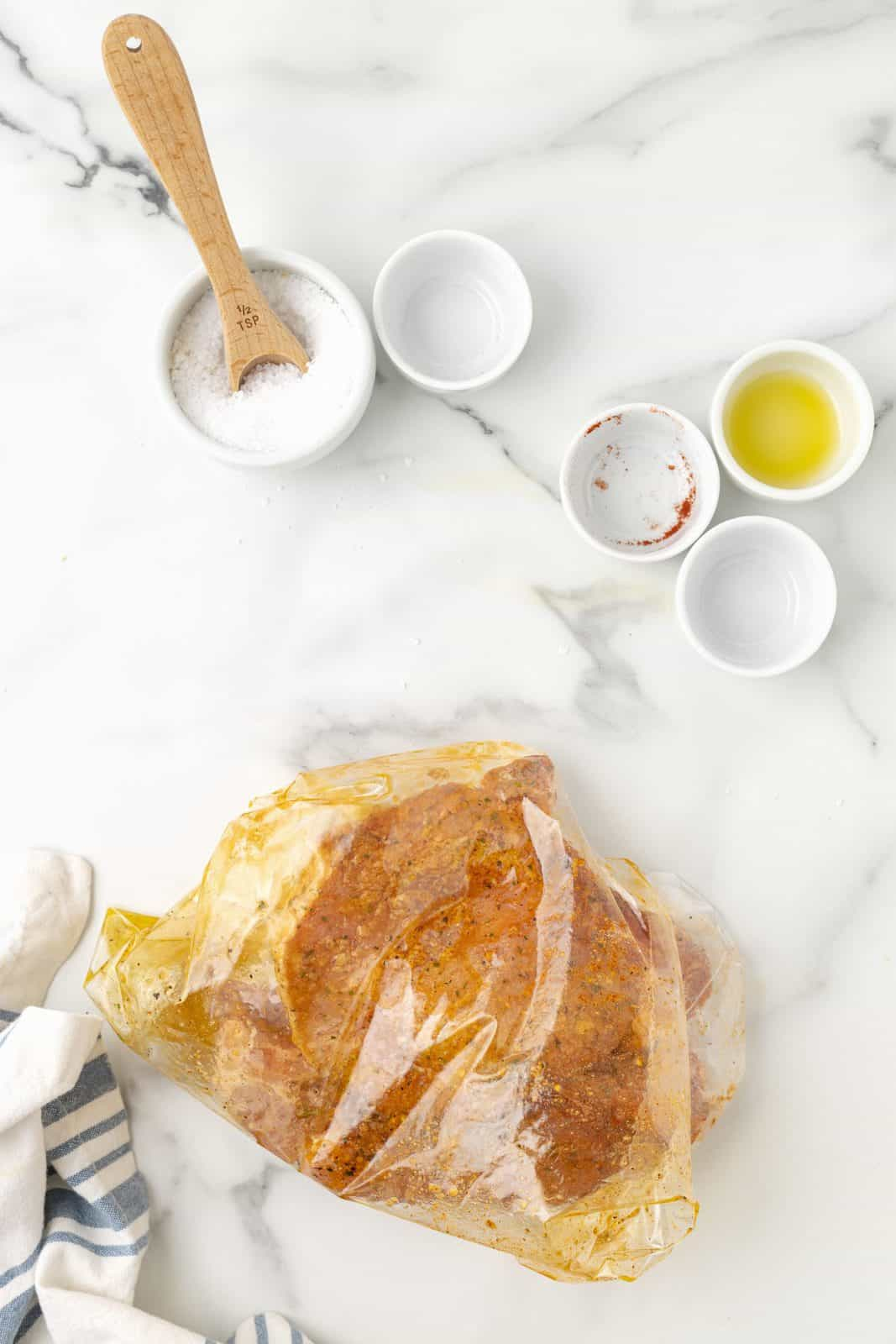 Pork chops shaken up with ingredients in bag to coat.