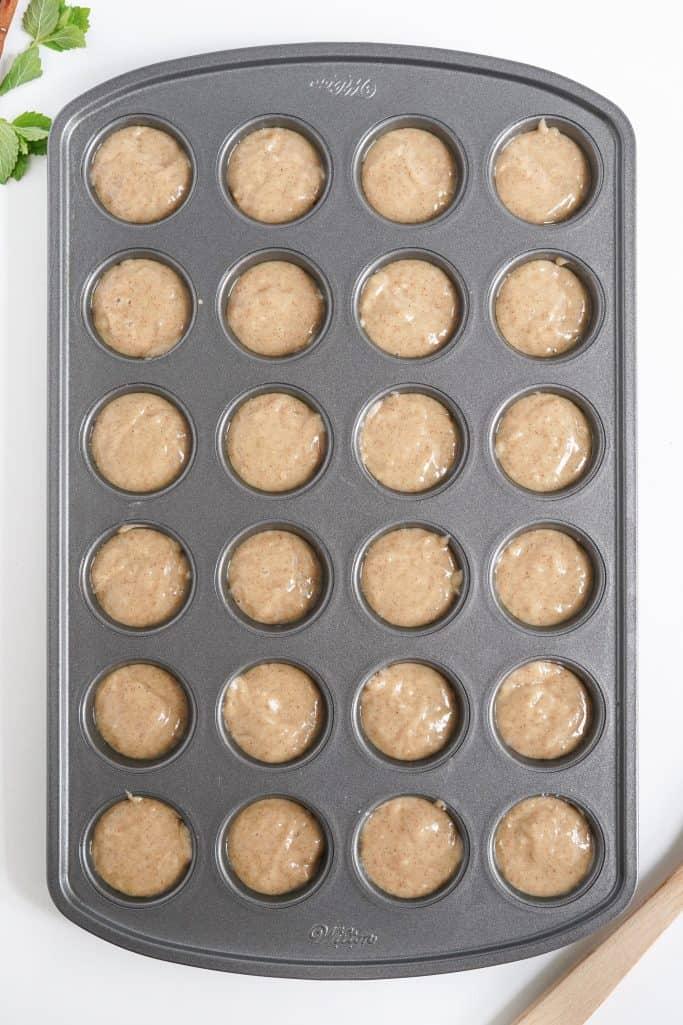 Donut batter in prepared mini muffin tin.