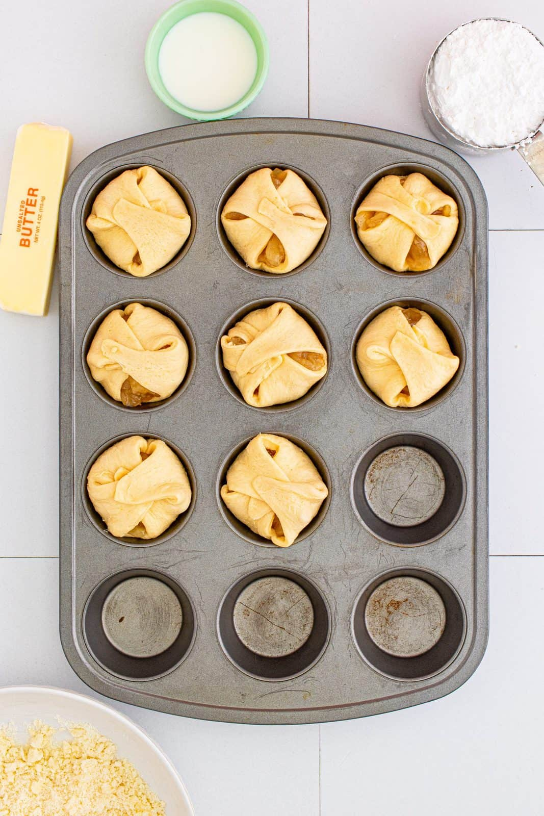 Crescent squares folded over apple pie filling in muffin tin.