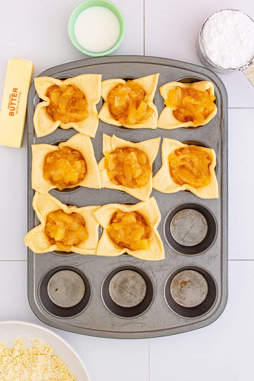 Apple pie filling added to crescent squares in muffin tin.