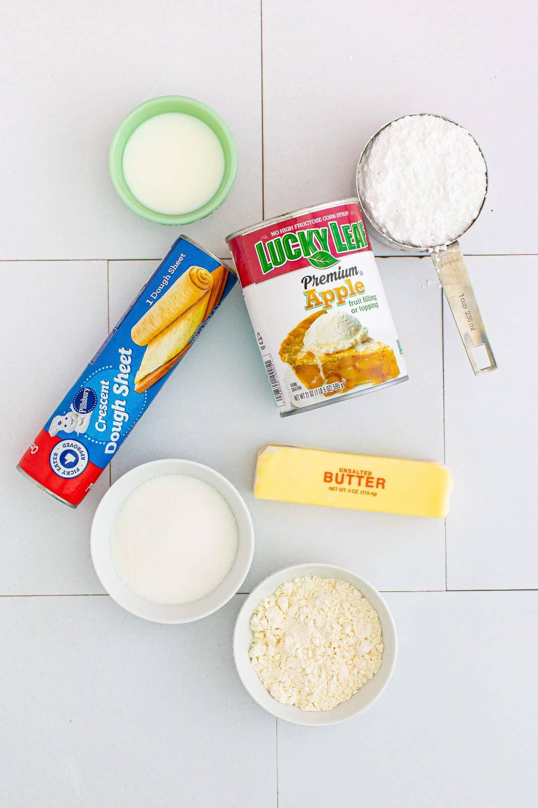 Ingredients needed: canned apple pie filling, granulated sugar, all-purpose flour, unsalted butter, crescent roll dough sheet, powdered sugar and whole milk.