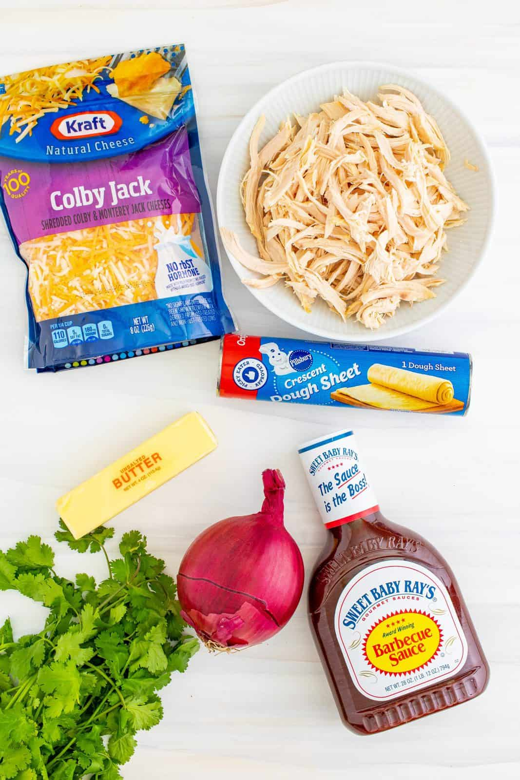 Ingredients needed: unsalted butter, red onion, shredded chicken, bbq sauce, cilantro, crescent roll dough sheet and colby jack cheese.