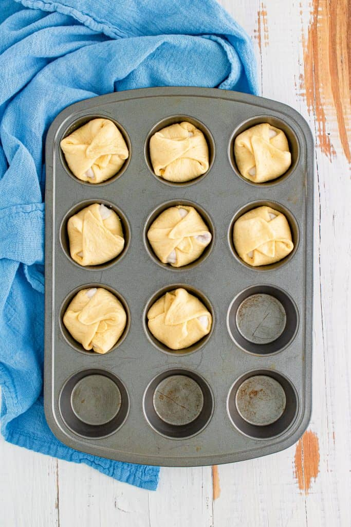 Crescent Squares folded over gravy to seal in muffin pan.