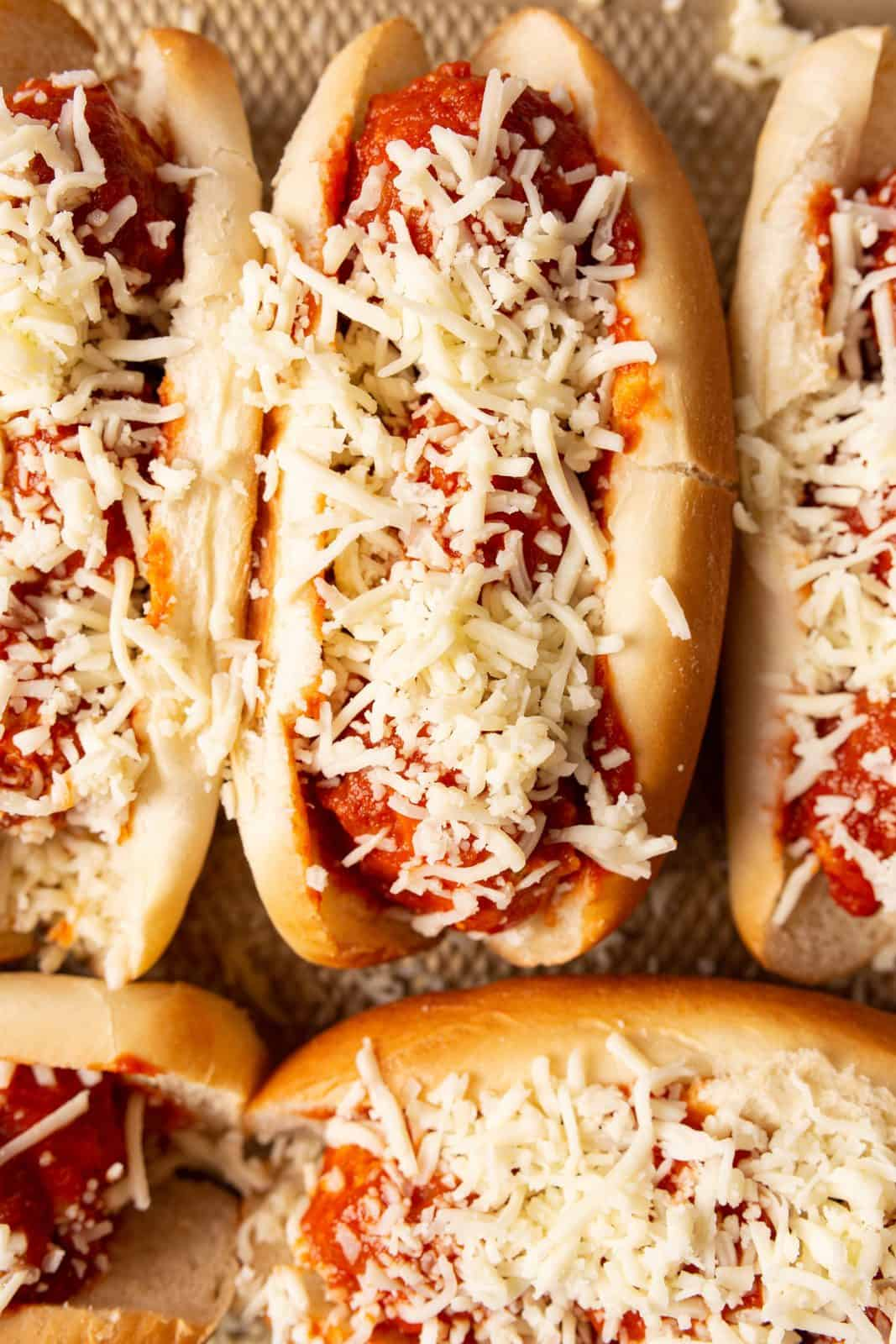Cheese sprinkled on meatballs in buns.