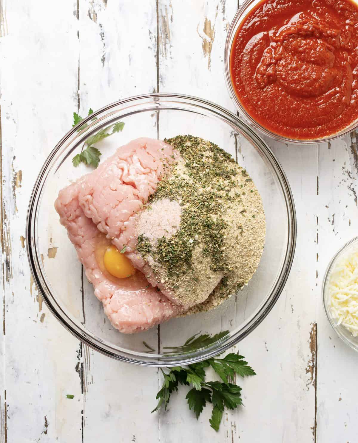 Ground turkey, italian breadcrumbs, eggs, italian seasoning and salt added to clear bowl.
