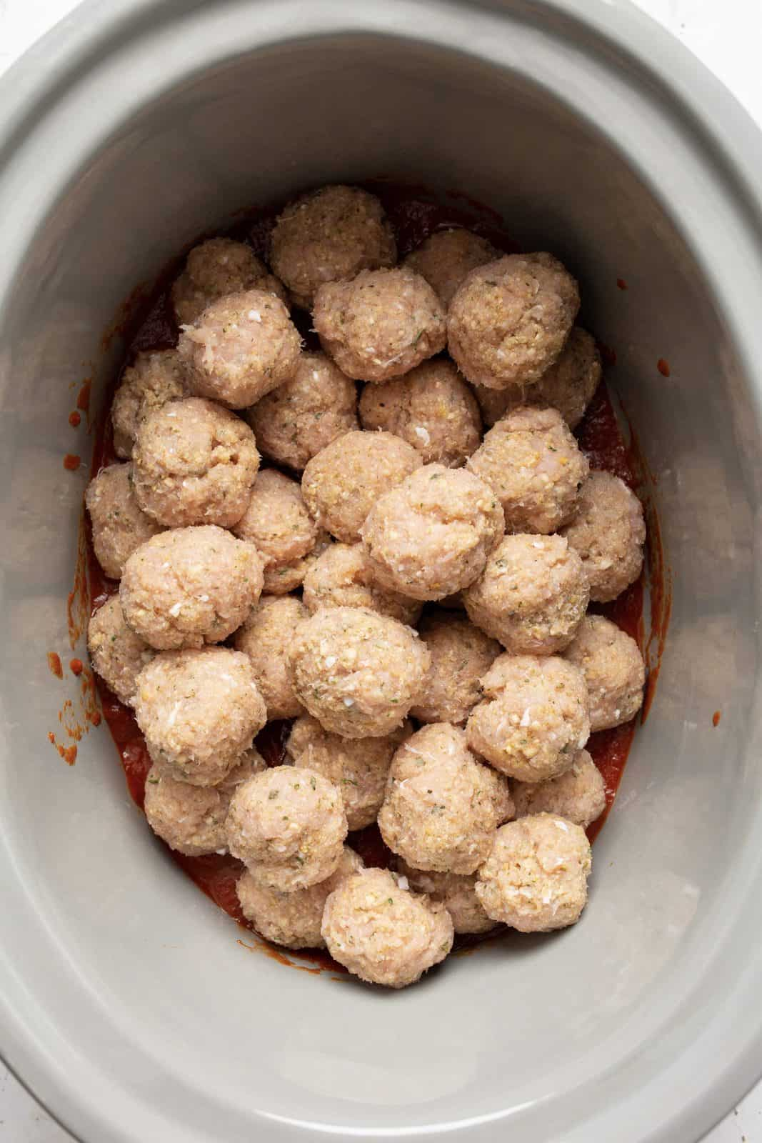 Meatballs in crock pot over a layer of sauce.