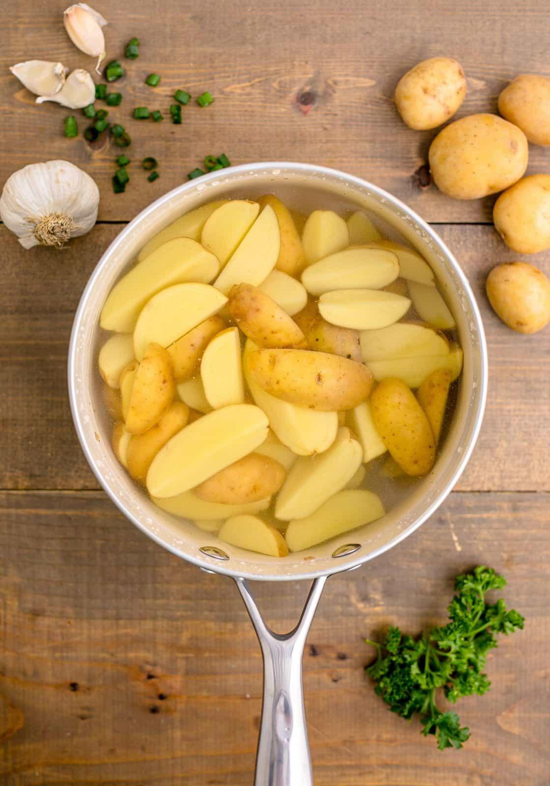 Potatoes being par-boiled in pan.