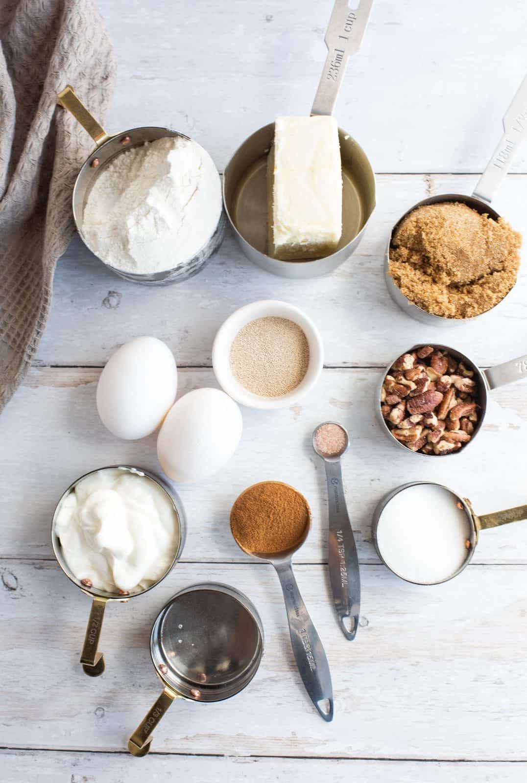 Ingredients needed: instant yeast, water, granulated sugar, sour cream, all-purpose flour, salt, butter, eggs, brown sugar, pecans and cinnamon.