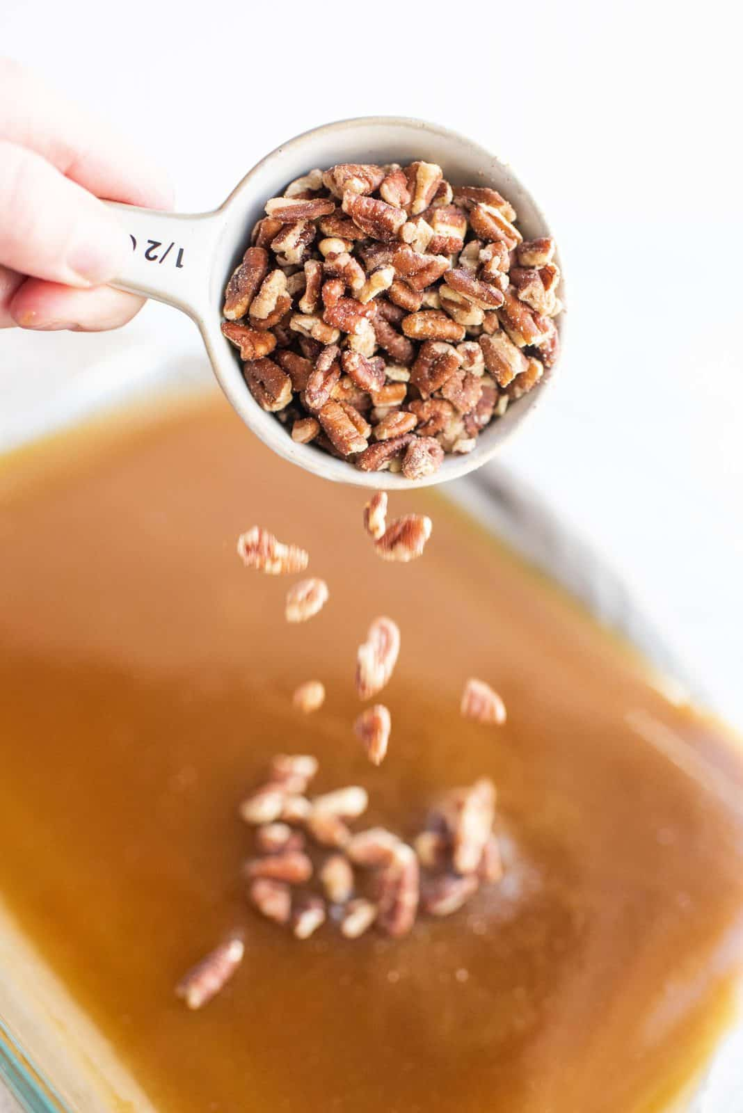 Pecans being added to baking dish.