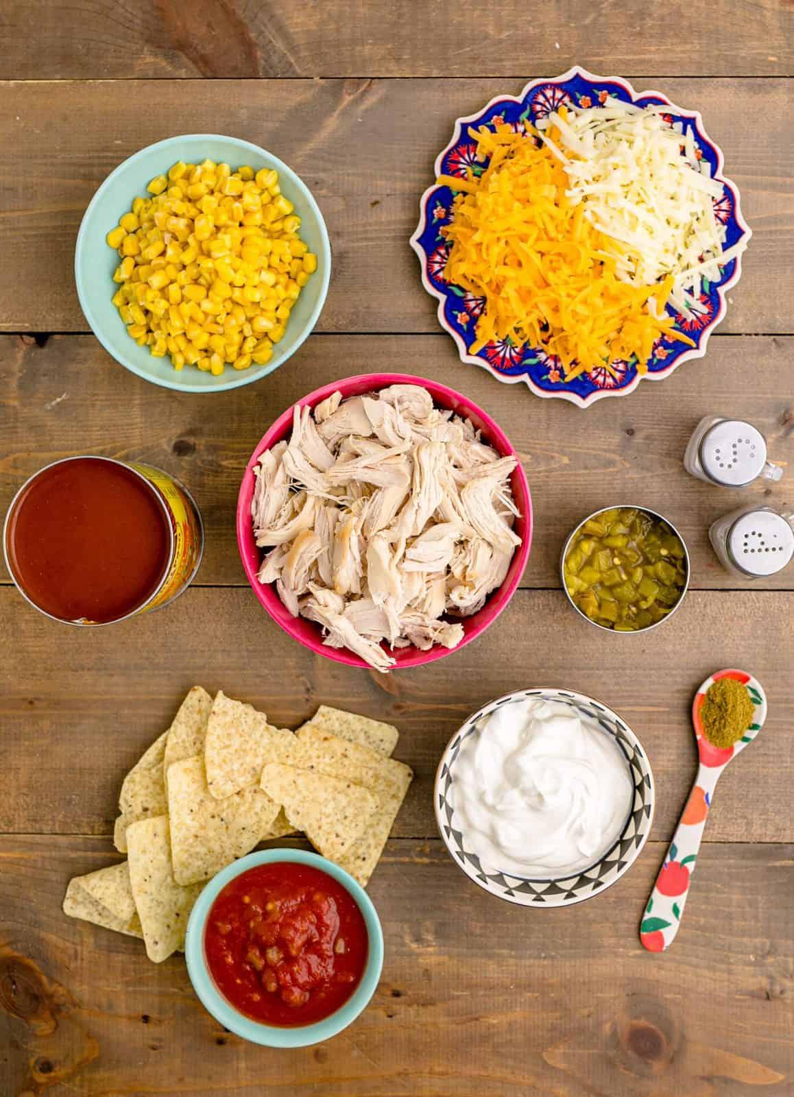 Ingredients needed: enchilada sauce green chilis, salsa, frozen corn, sour cream, cumin, salt, pepper, shredded chicken, tortilla chips, cheddar cheese, pepper jack cheese and optional garnishes.