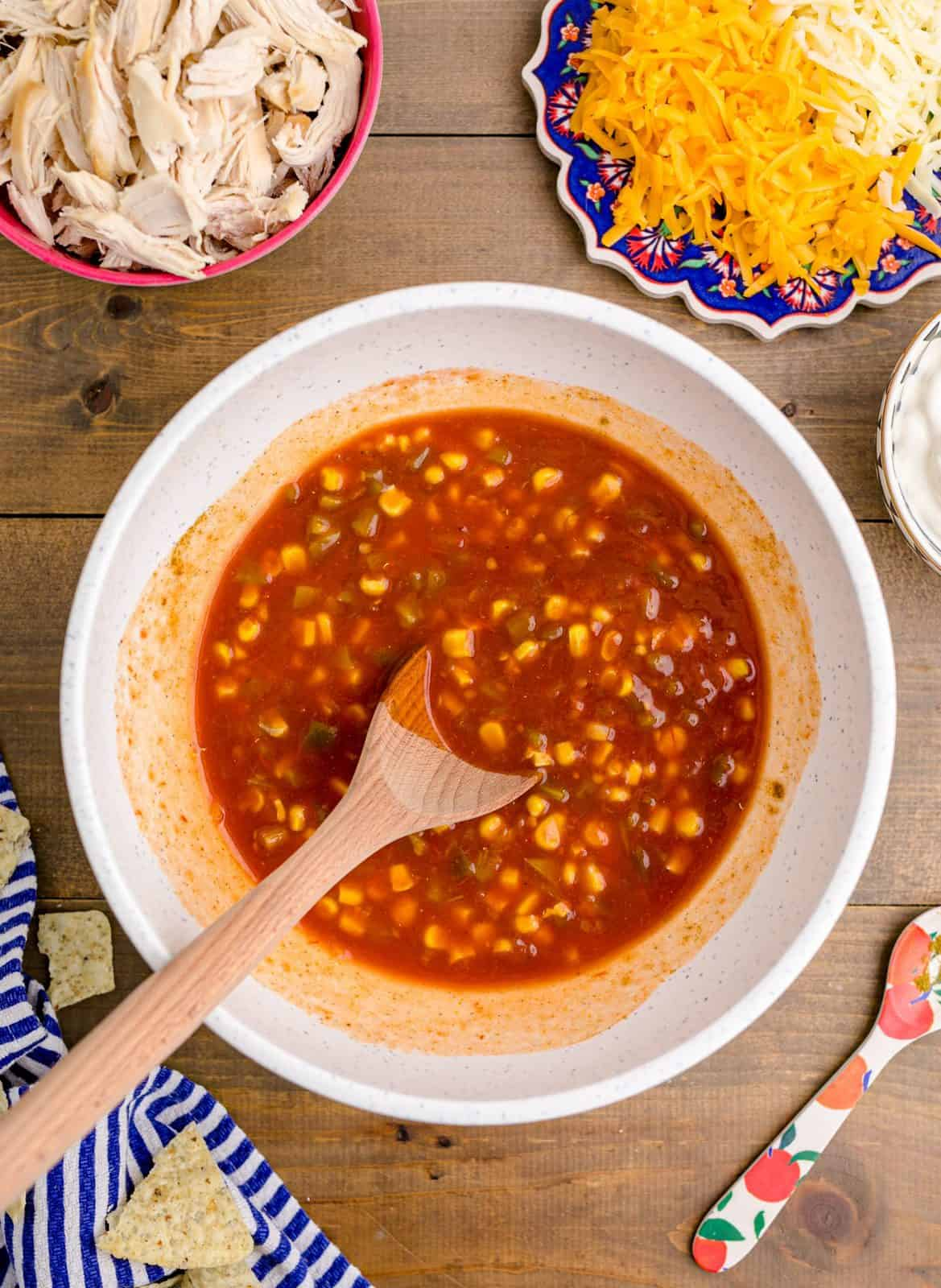 Enchilada sauce, drained green chilis, salsa, thawed corn, cumin, salt, and pepper added to white bowl and mixed together.