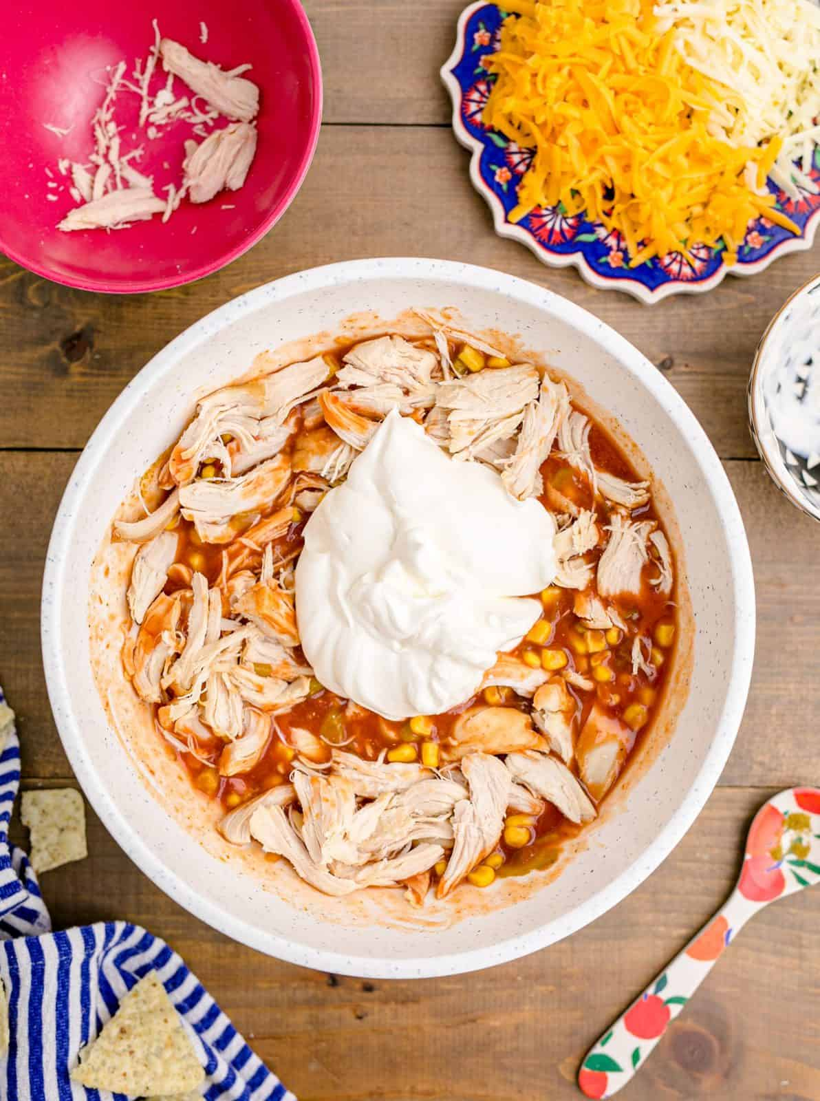 Sour cream and chicken added to mixture in white bowl.
