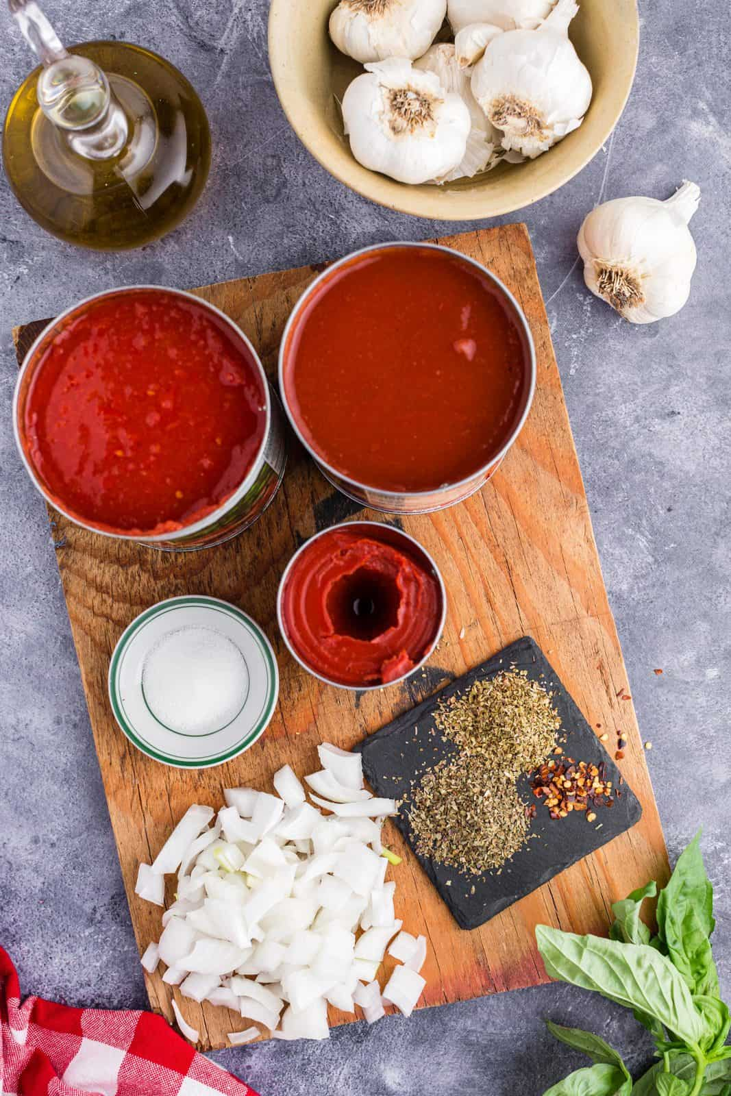 Ingredients needed: olive oil, yellow onion, garlic, dried basil, dried oregano, crushed red pepper flakes, tomato paste, tomato sauce, crushed tomatoes, granulated sugar, and parmesan cheese.