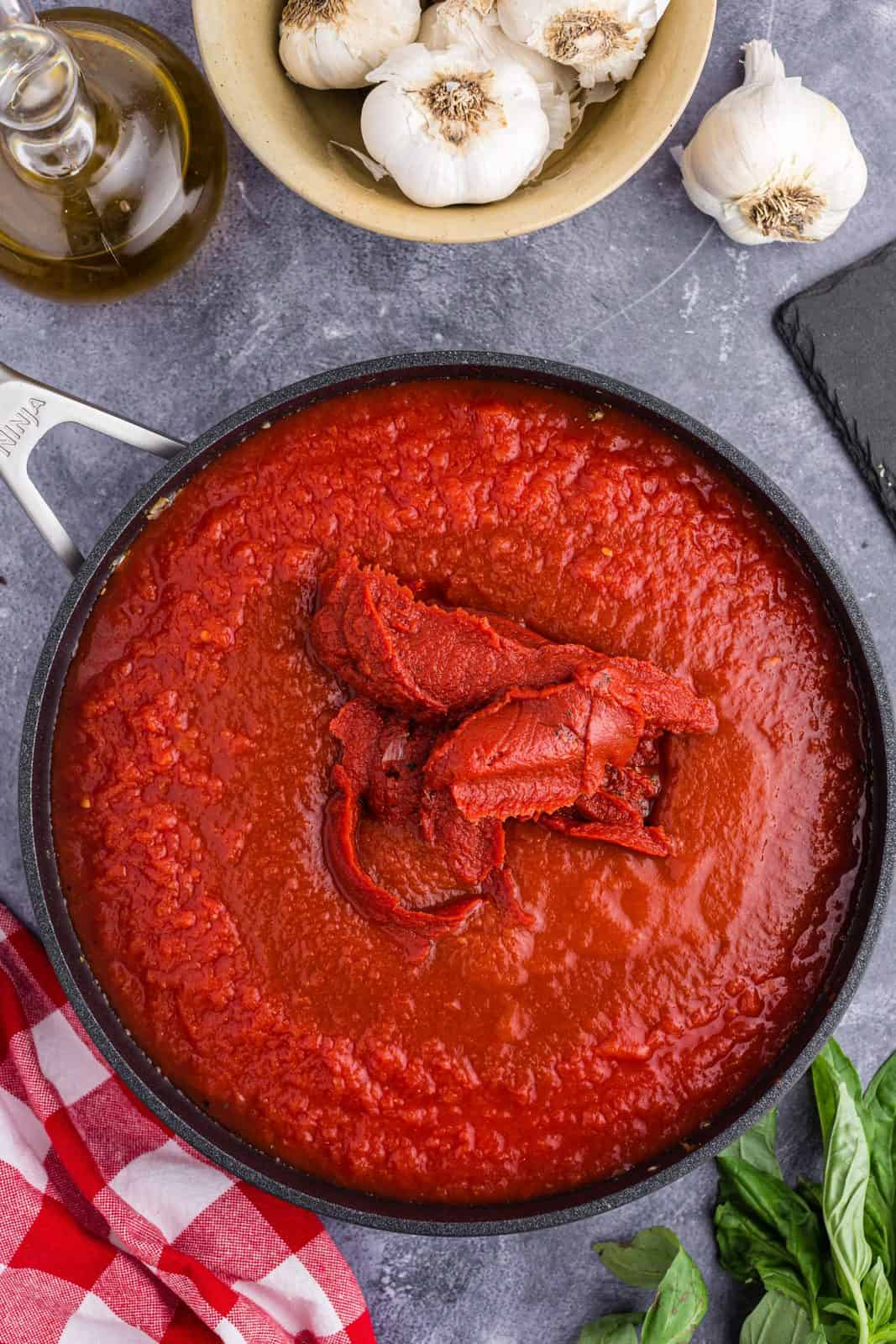 Tomato paste, tomato sauce and crushed tomatoes added to pan.