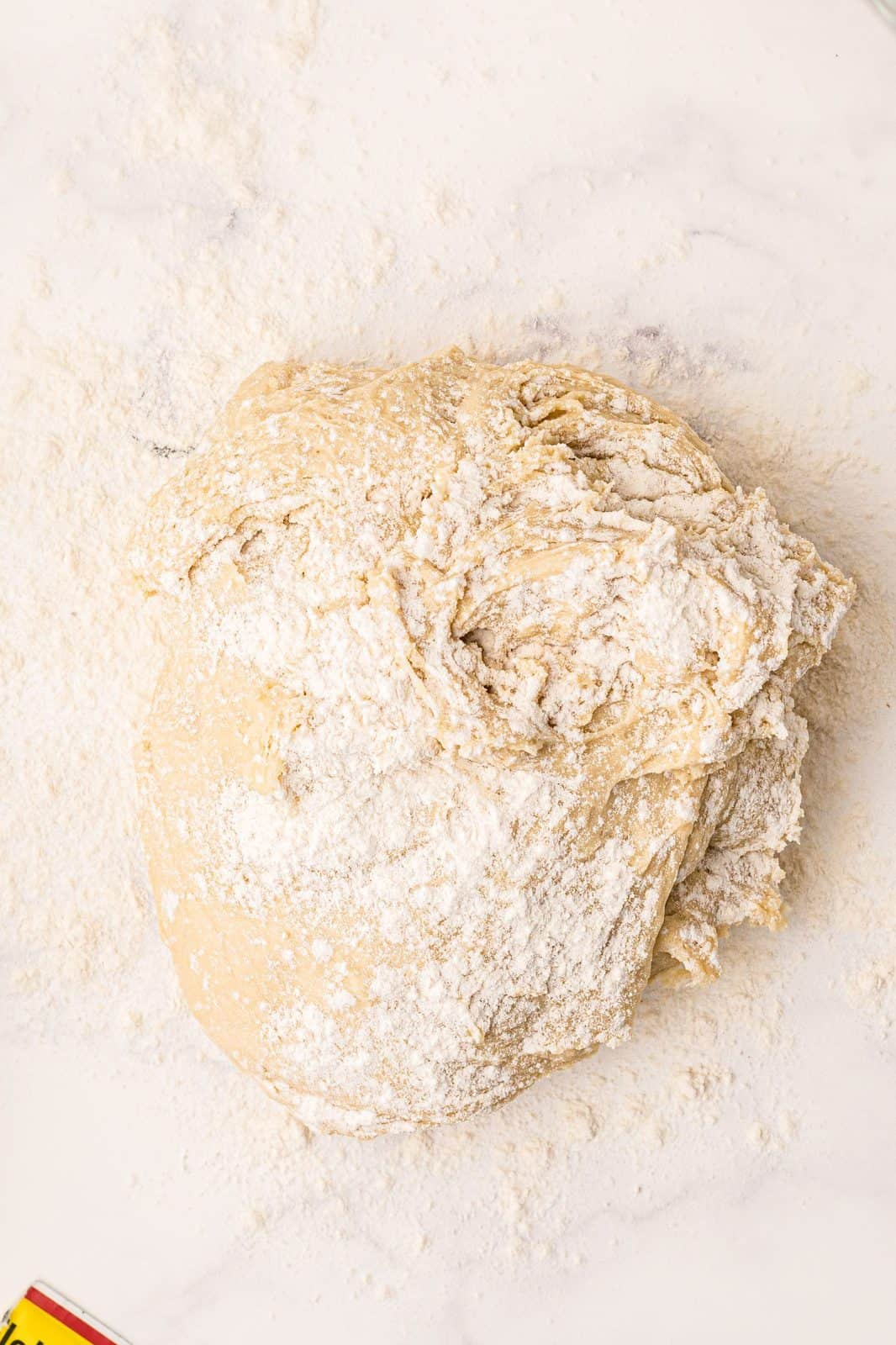 Dough added to floured surface being kneaded.