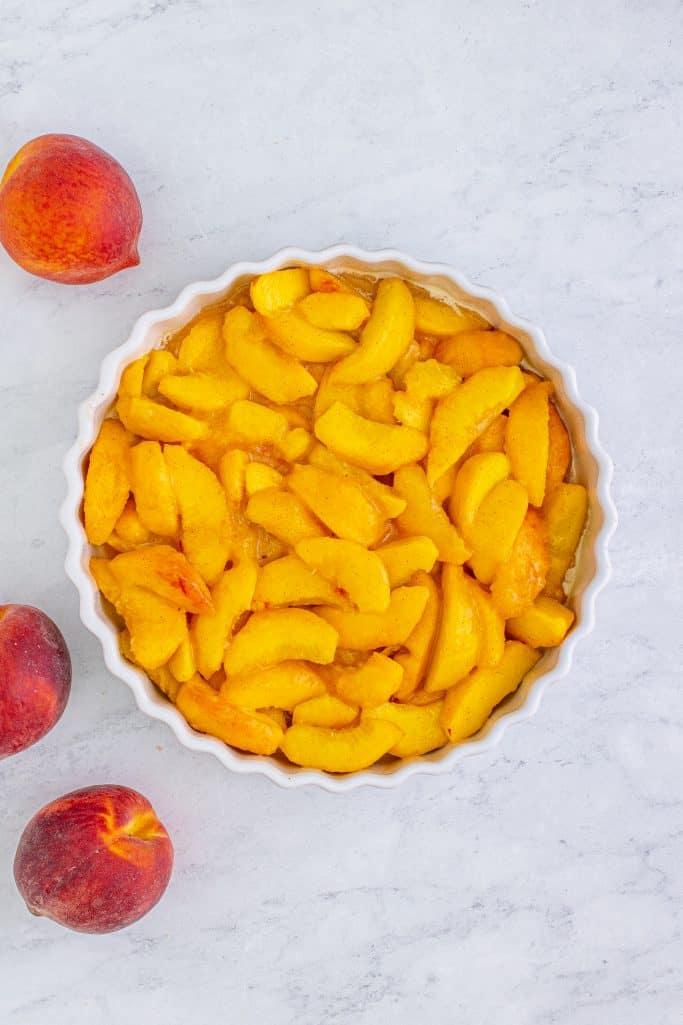 Peaches added to white baking dish.