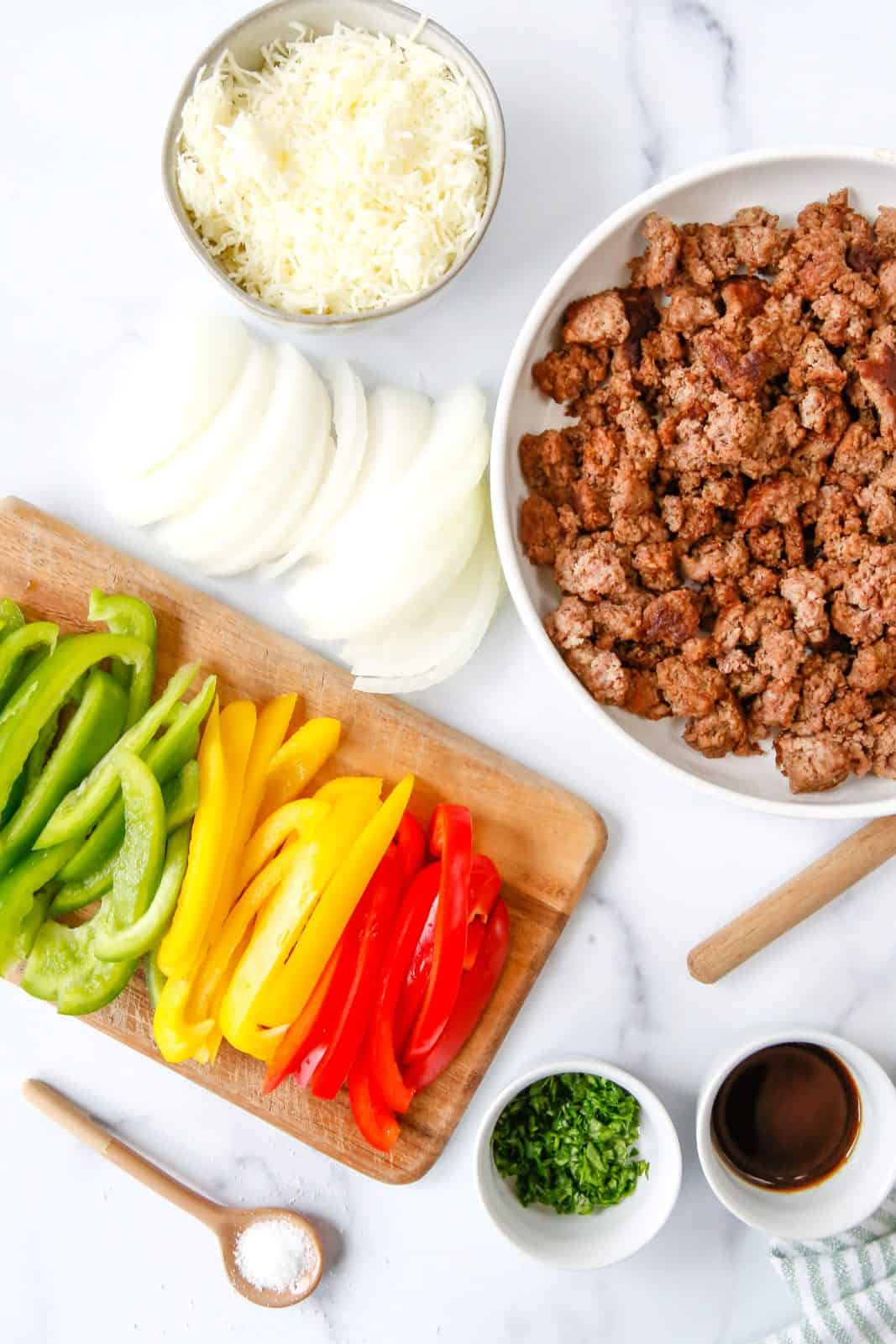 Ingredients needed: ground beef, butter, yellow onion, green bell pepper, red bell pepper, yellow bell pepper, beef broth, worcestershire sauce, garlic powder, salt, pepper, provolone or mozzarella cheese and minced parsley.