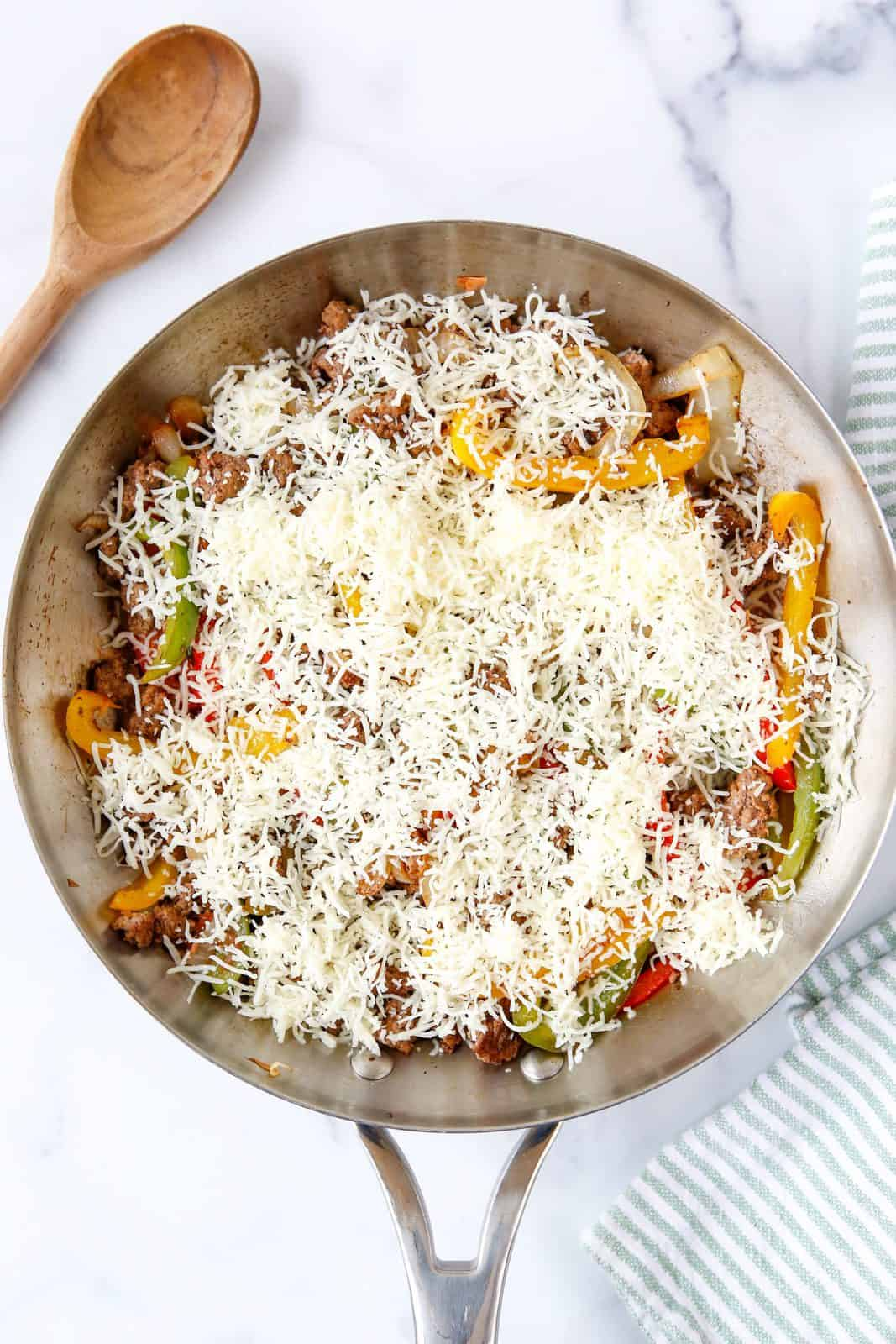 Shredded cheese added to top of all the ingredients in the skillet.
