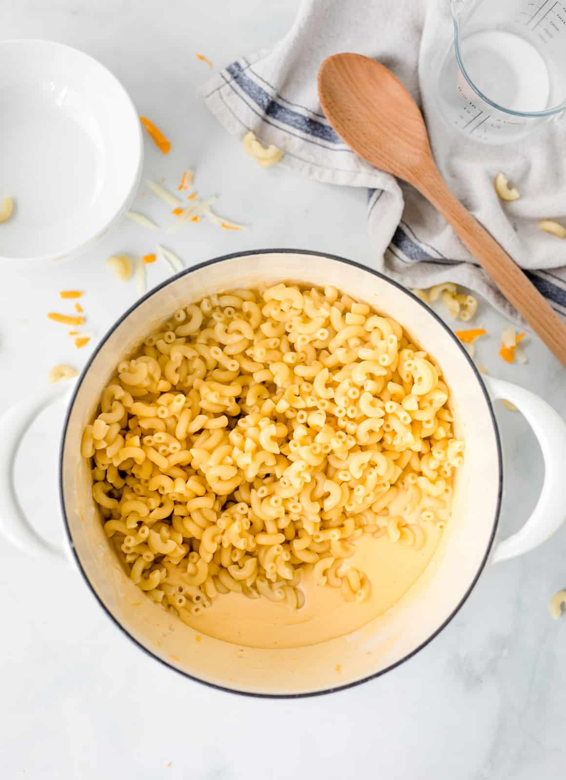 Pasta added to the cheese sauce in pan.