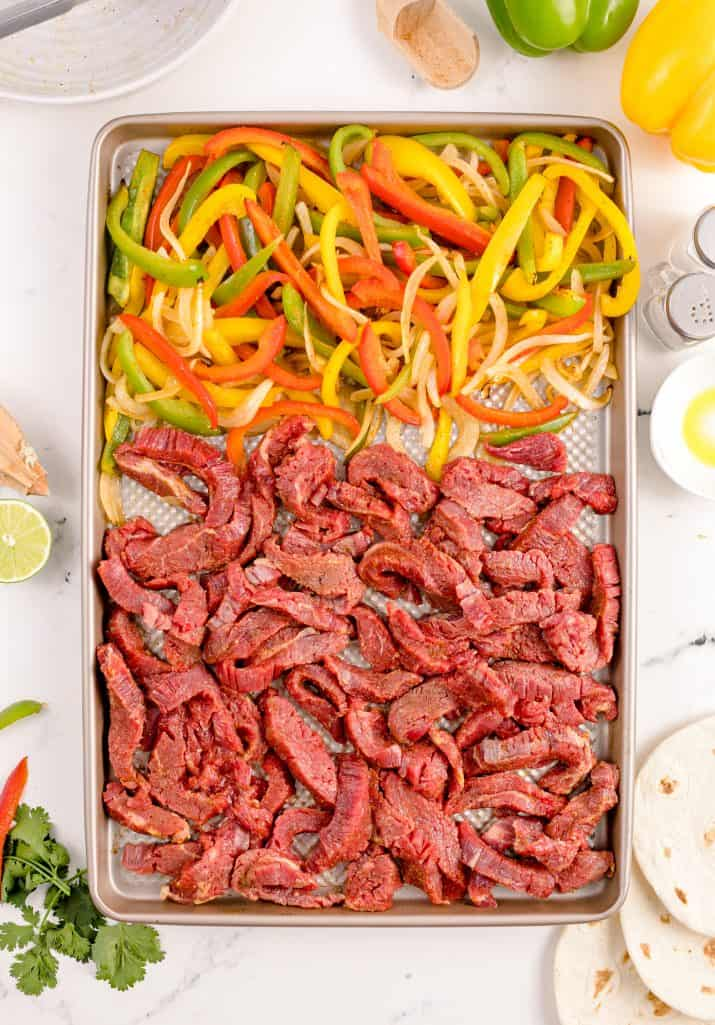 Beef added to sheet pan with vegetables.