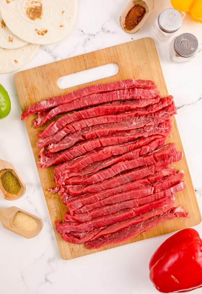 Cut up steak on wooden cutting board.