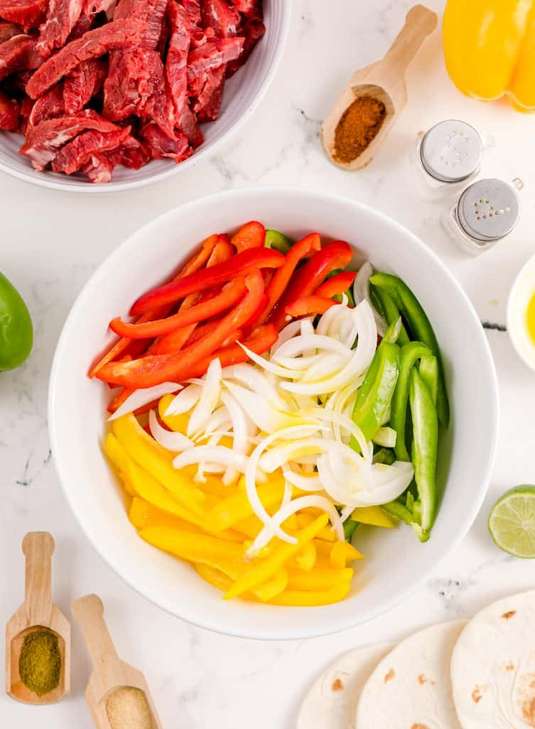 Sliced peppers in onions in white bowl.