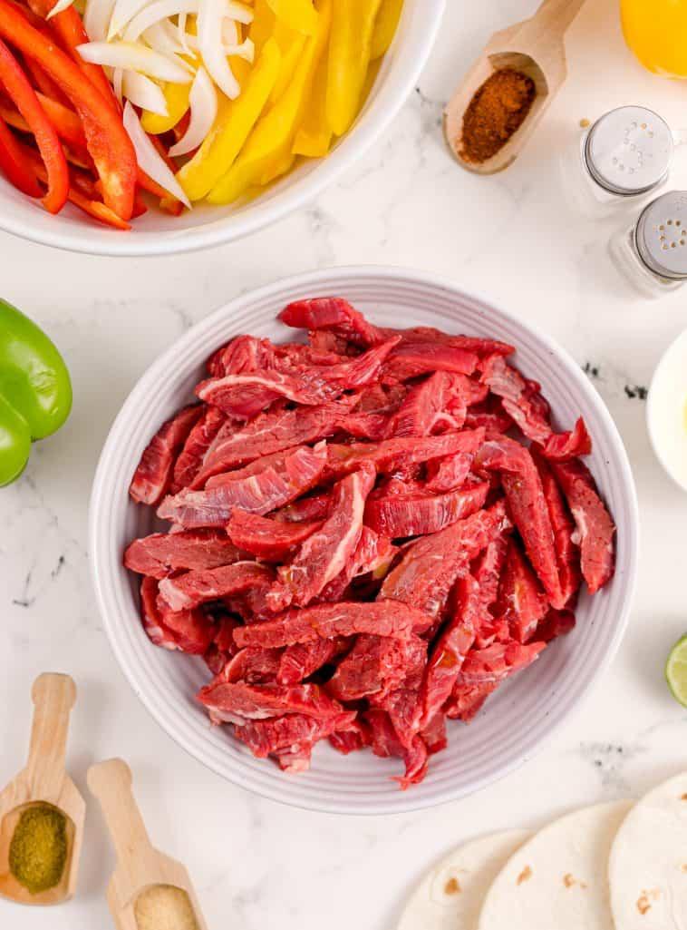 Sliced steak in white bowl.