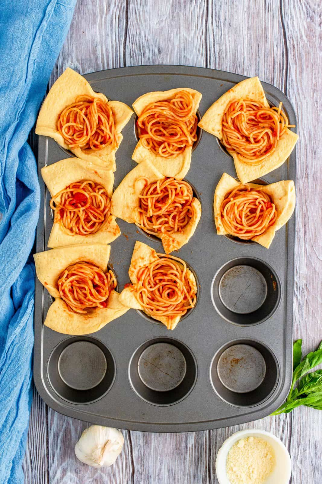Spaghetti added to crescent squares in muffin tin.