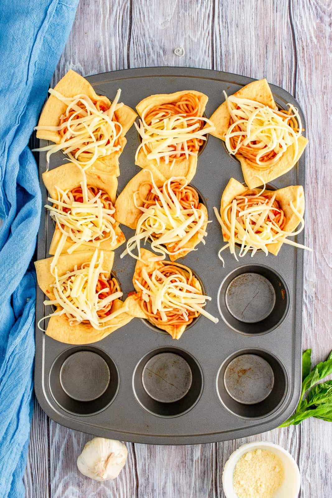 shredded mozzarella cheese added to top of spaghetti inside crescent roll cups.