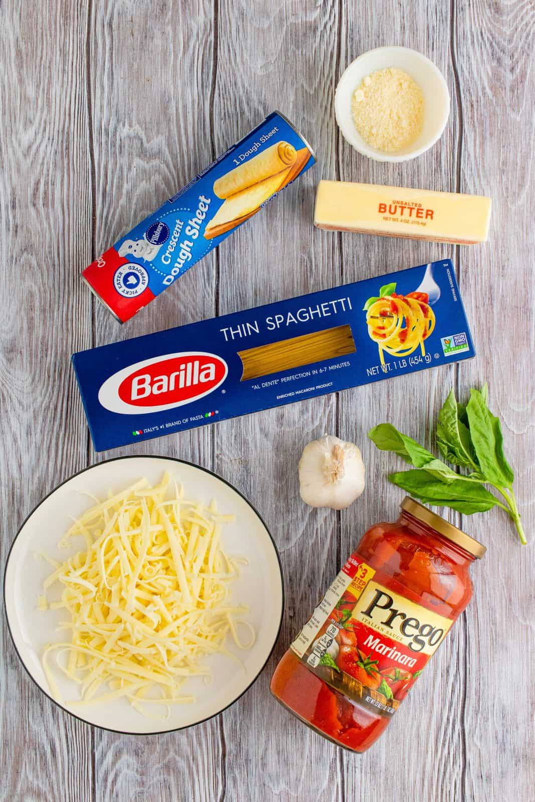 Ingredients needed: thin spaghetti noodles, marinara sauce, crescent roll dough sheet, shredded mozzarella cheese, unsalted butter, grated parmesan cheese, basil leaves and garlic.