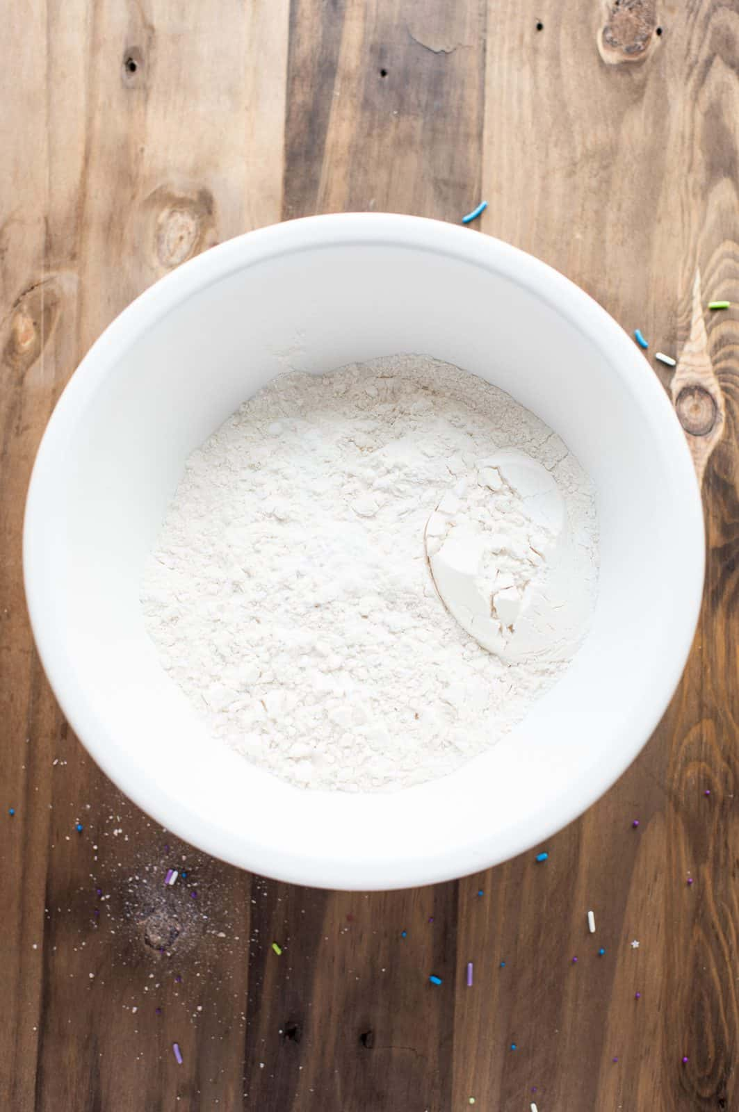 All-purpose flour, baking powder, baking soda and salt whisked together in white bowl.