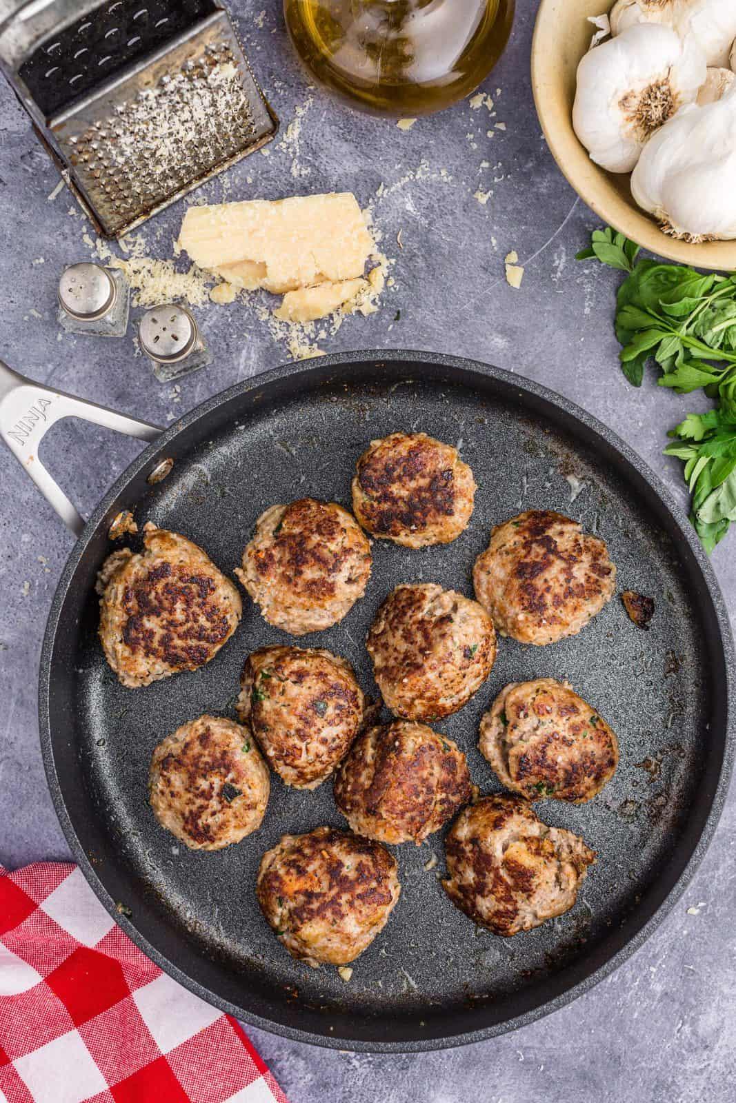 Browned meatballs in skillet.