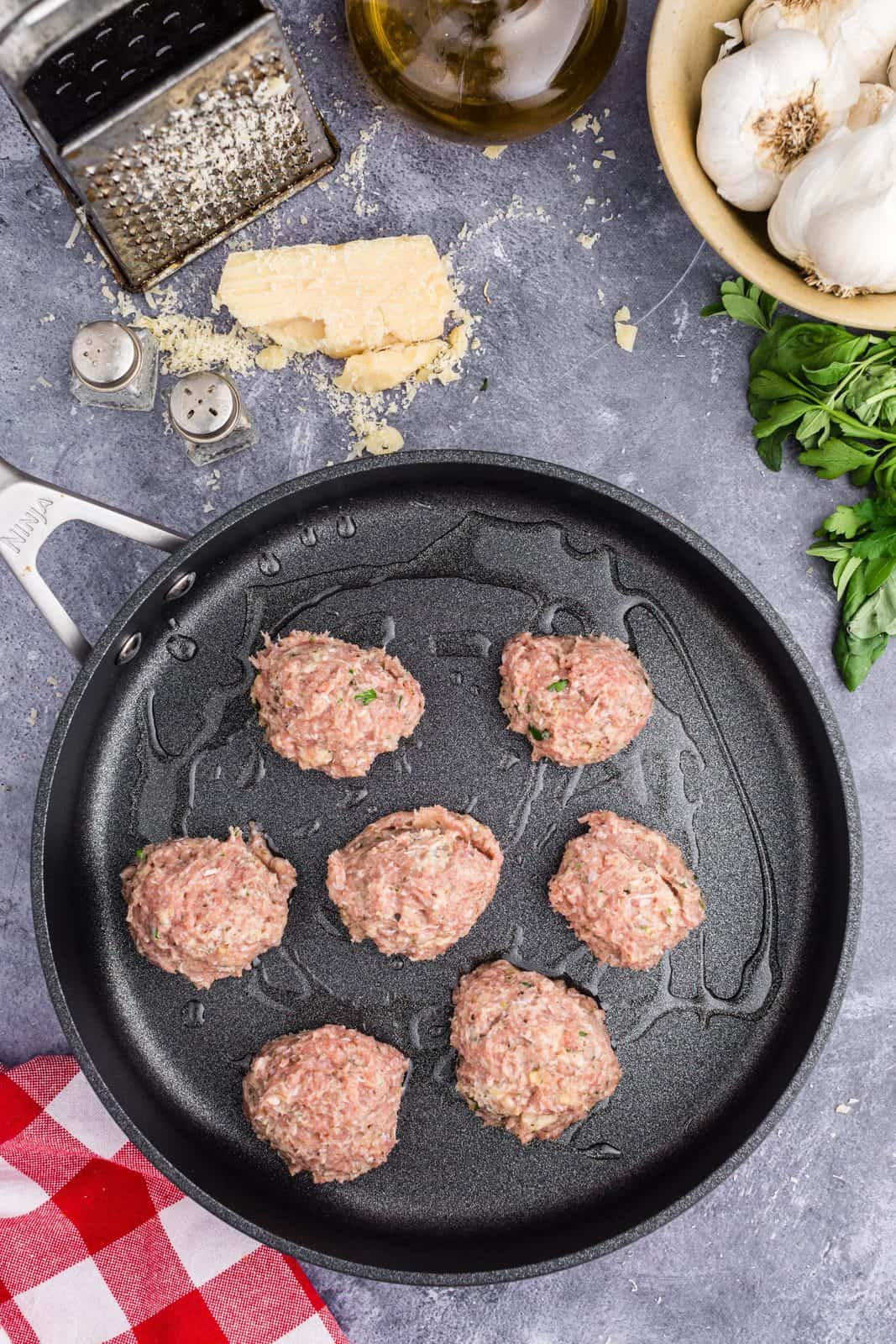 Meatballs portioned and added to oiled skillet.