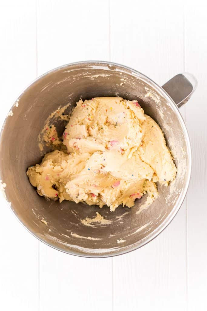 Cookies mixed into dough in bowl of stand mixer.