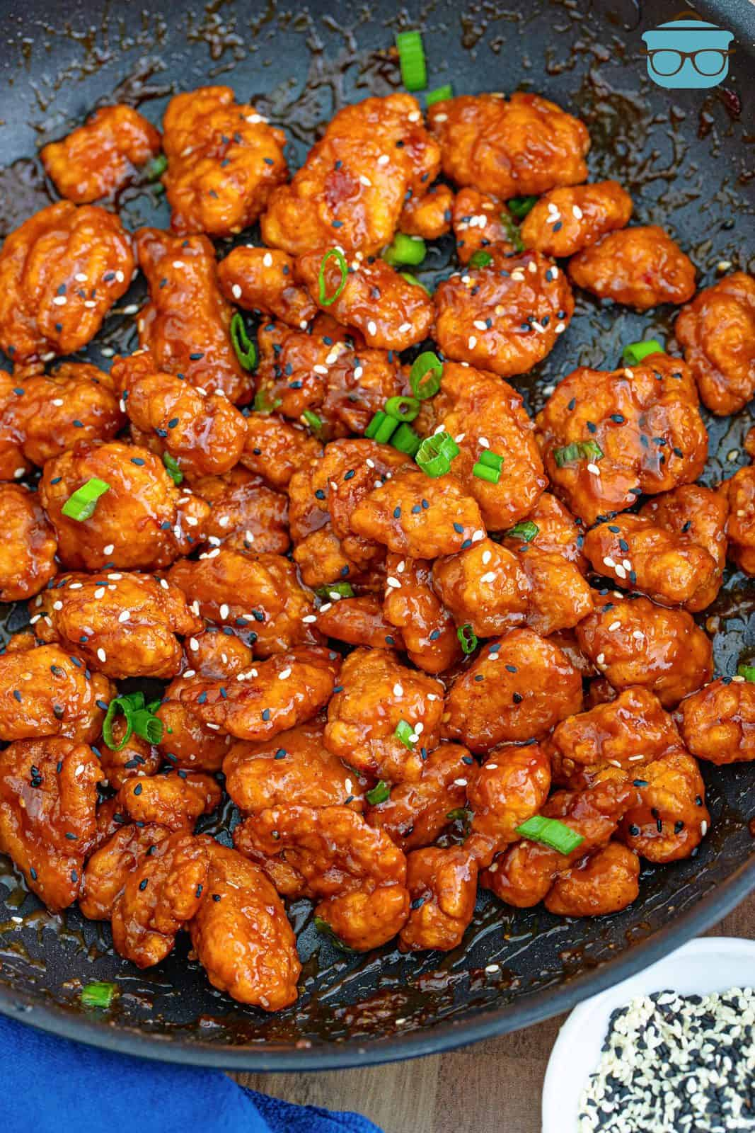 Easy General Tso's Chicken in skillet with sesame seeds and scallions.