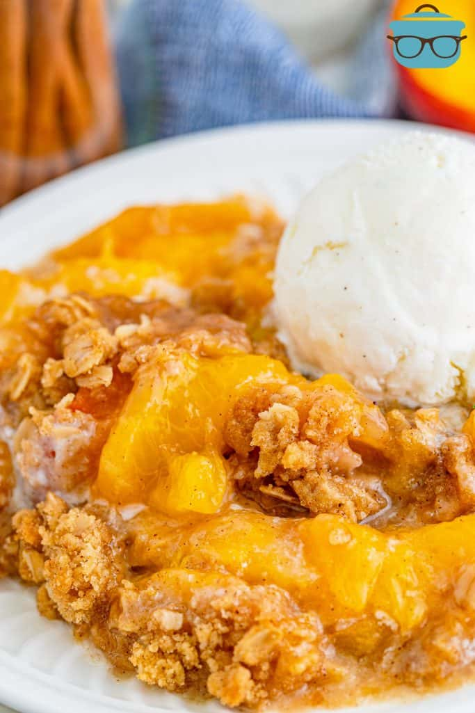 Easy Fresh Peach Crisp on plate topped with ice cream.